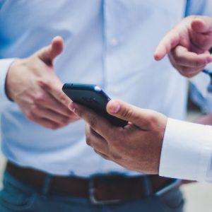 Lead-Generierung durch Corporate Blogging. Mann deutet auf Smartphone